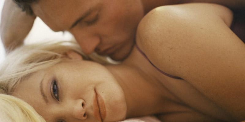 Um casal na cama fazendo sexo